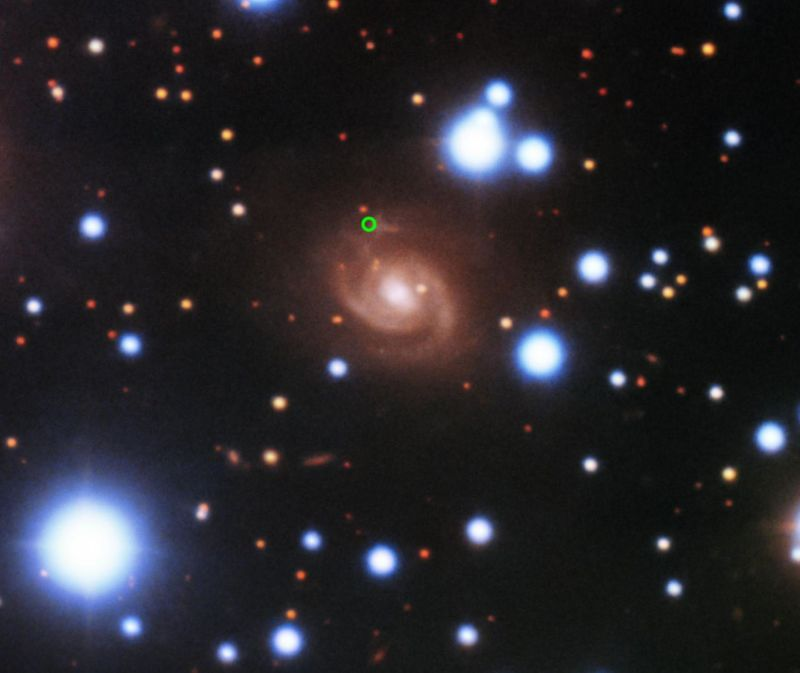 Image of a galaxy with a small green circle.