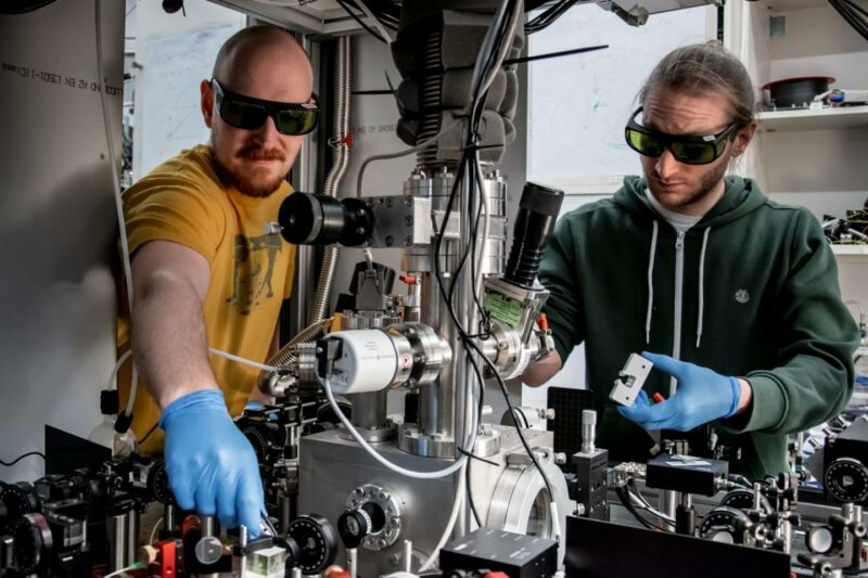 Image of two scientists wearing gloves and sunglasses in amidst lab equipment.