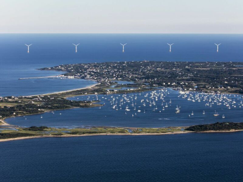 Image of wind turbines in the waters beyond an island.