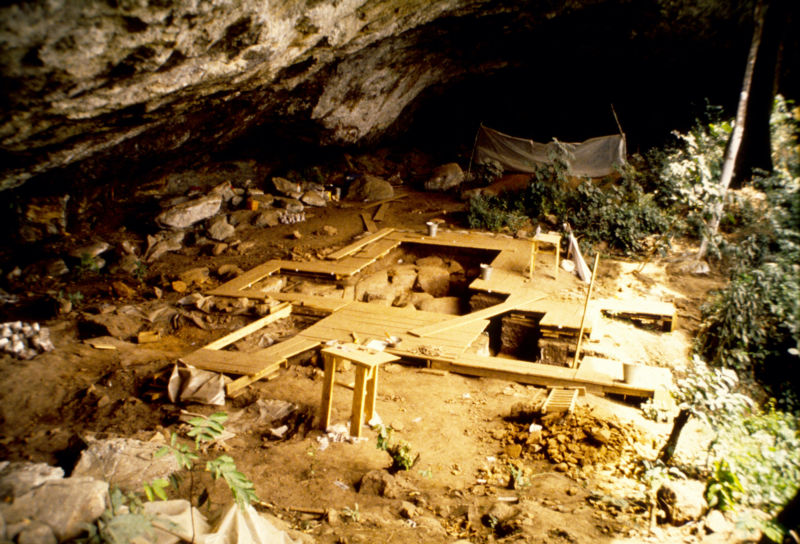 Image of boards surrounding trenches under a rock overhang.
