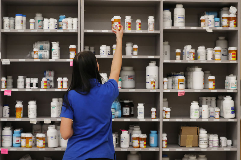 A pharmacy technician grabs a bottle of drugs off a shelf at the central pharmacy of Intermountain Heathcare on September 10, 2018 in Midvale, UT.