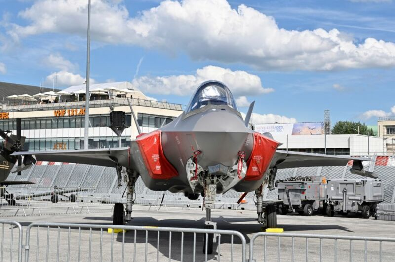 A jet fighter its on a runway behind low metal fencing.