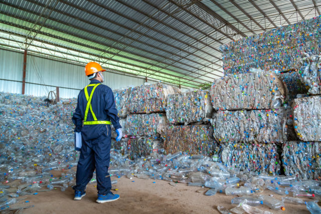 A recycling factory worker in Thailand surveys the scale of plastics being disposed.