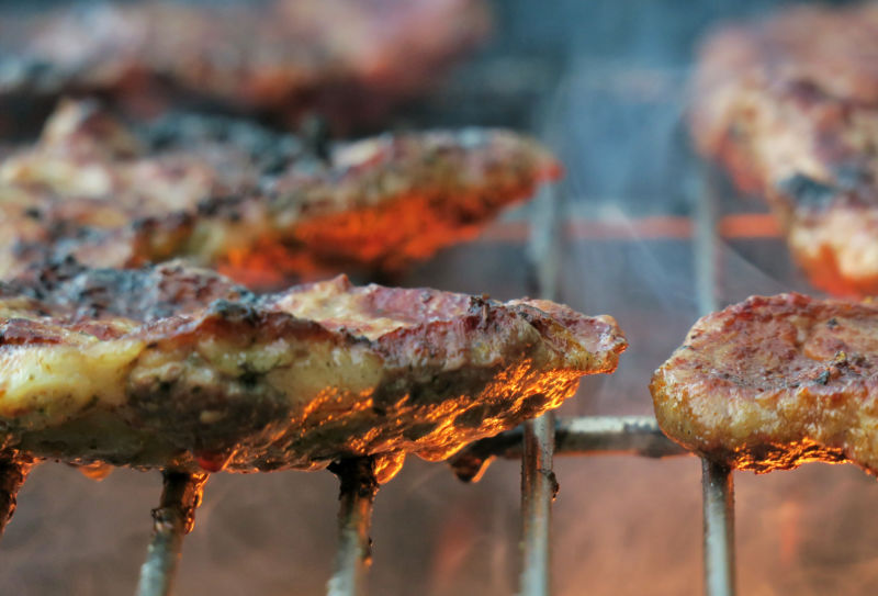 A close-up of charred meat cooking on a grill with flames below and rising smoke