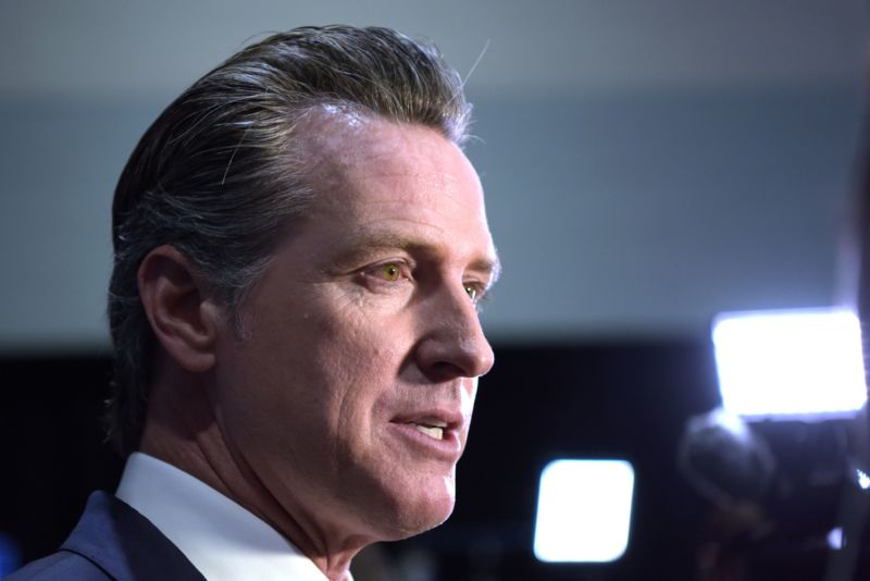 A close up of Newsom's face turned to face reporters not pictured, with camera lights in the background.