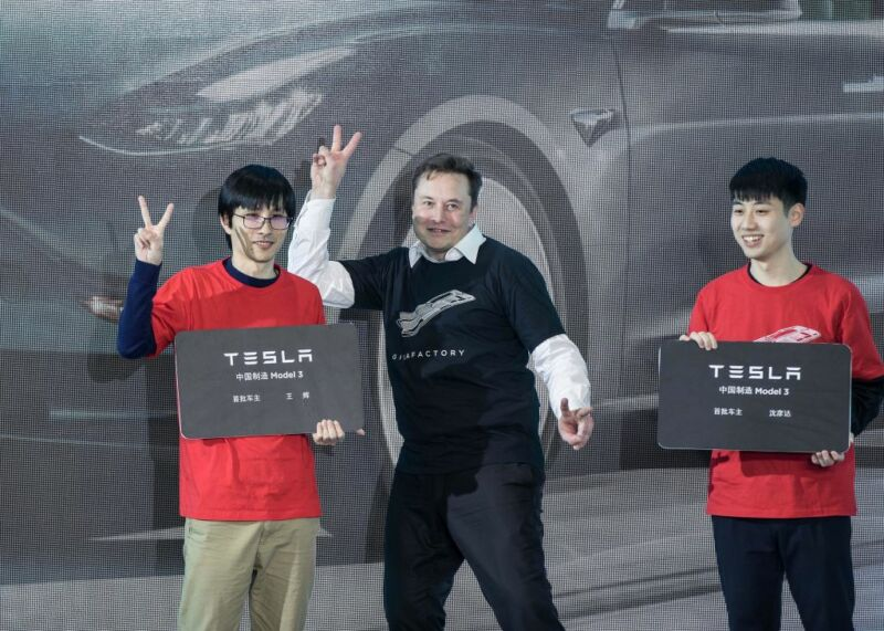 Elon Musk makes a peace sign with two Chinese men.