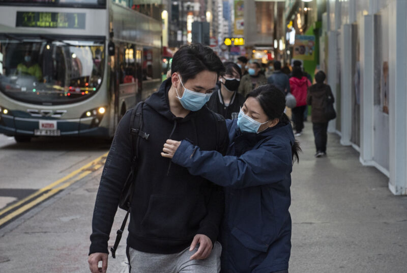 A couple wears ER-style masks on a crowded city street.