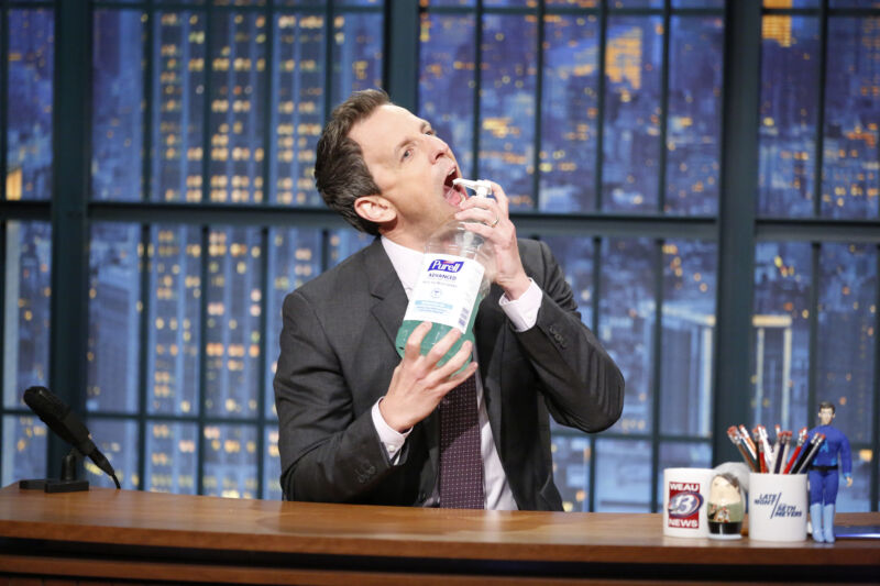 Comedian Seth Meyers sprays hand sanitizer into his mouth.