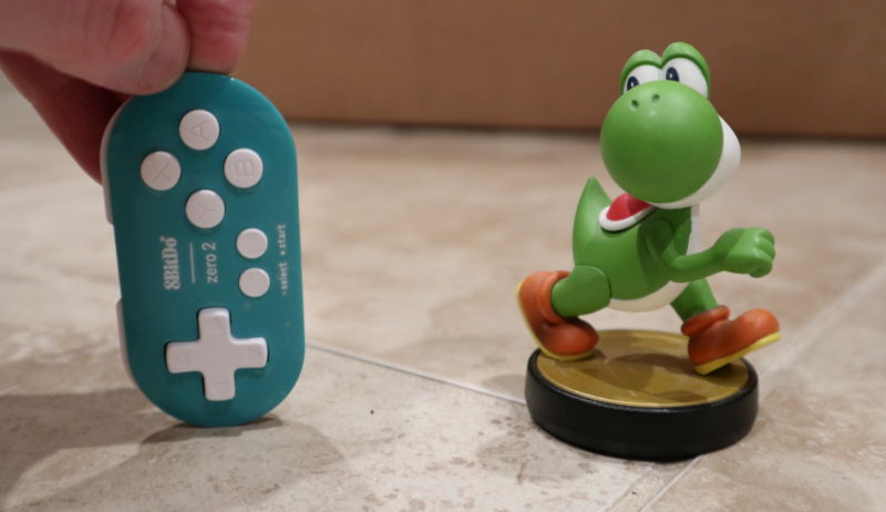 A hand holds a tiny video game controller next to a dinosaur figurine.