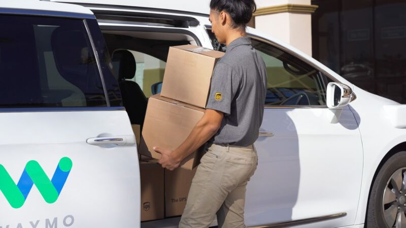 A UPS worker loads boxes into a Waymo van.