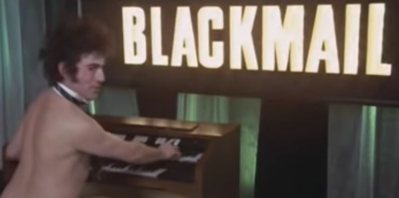 """Terry Jones playing the organ <i>au naturel</i> in Monty Python's """"Blackmail"""" sketch."""