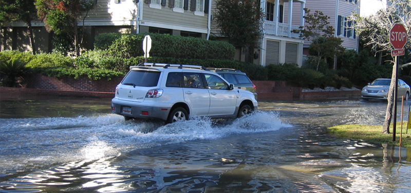 Image of a car driving through a flooded street.