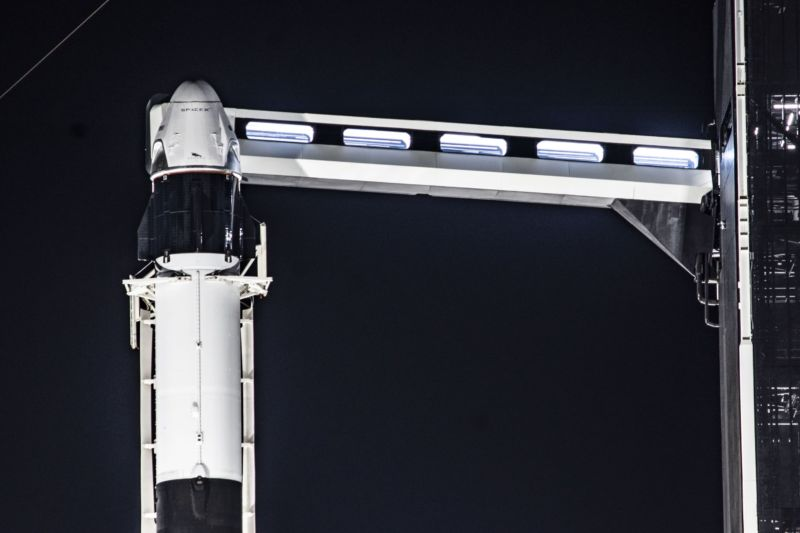 The Crew Dragon spacecraft sits atop a Falcon 9 rocket, with the crew access arm extended.