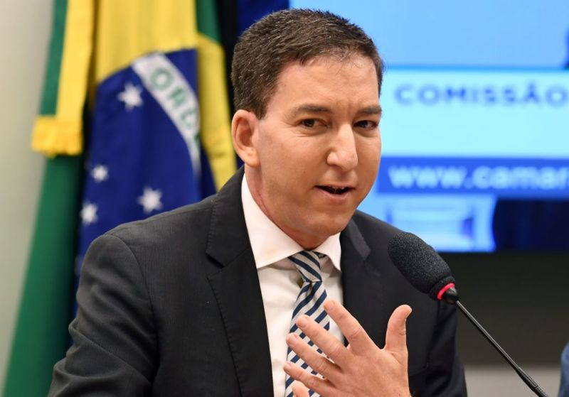 Glenn Greenwald speaking and gesturing with his hand at a government hearing in Brazil.
