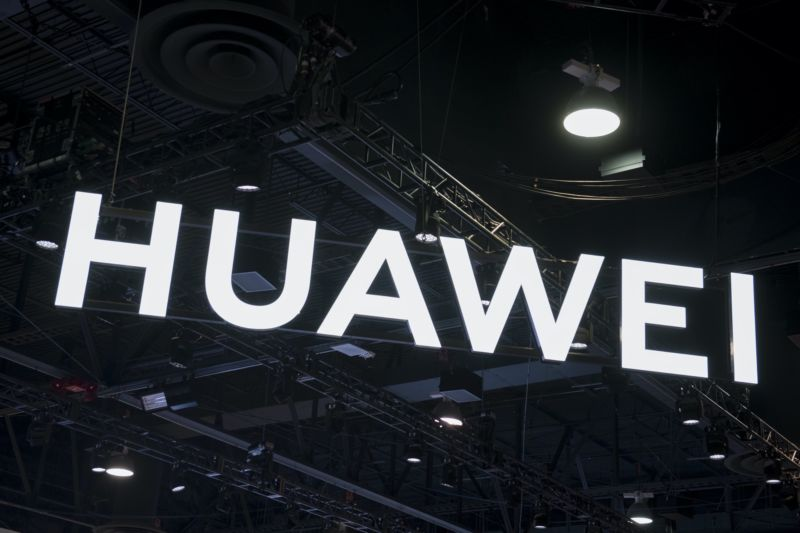 A Huawei sign hanging from the ceiling in a conference expo hall.