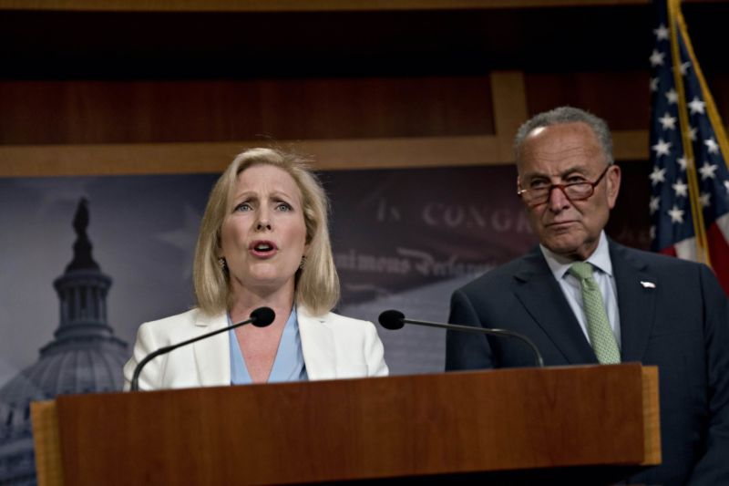 Senator Kirsten Gillibrand speaks at a podium during a news conference while Senate Minority Leader Chuck Schumer looks on.