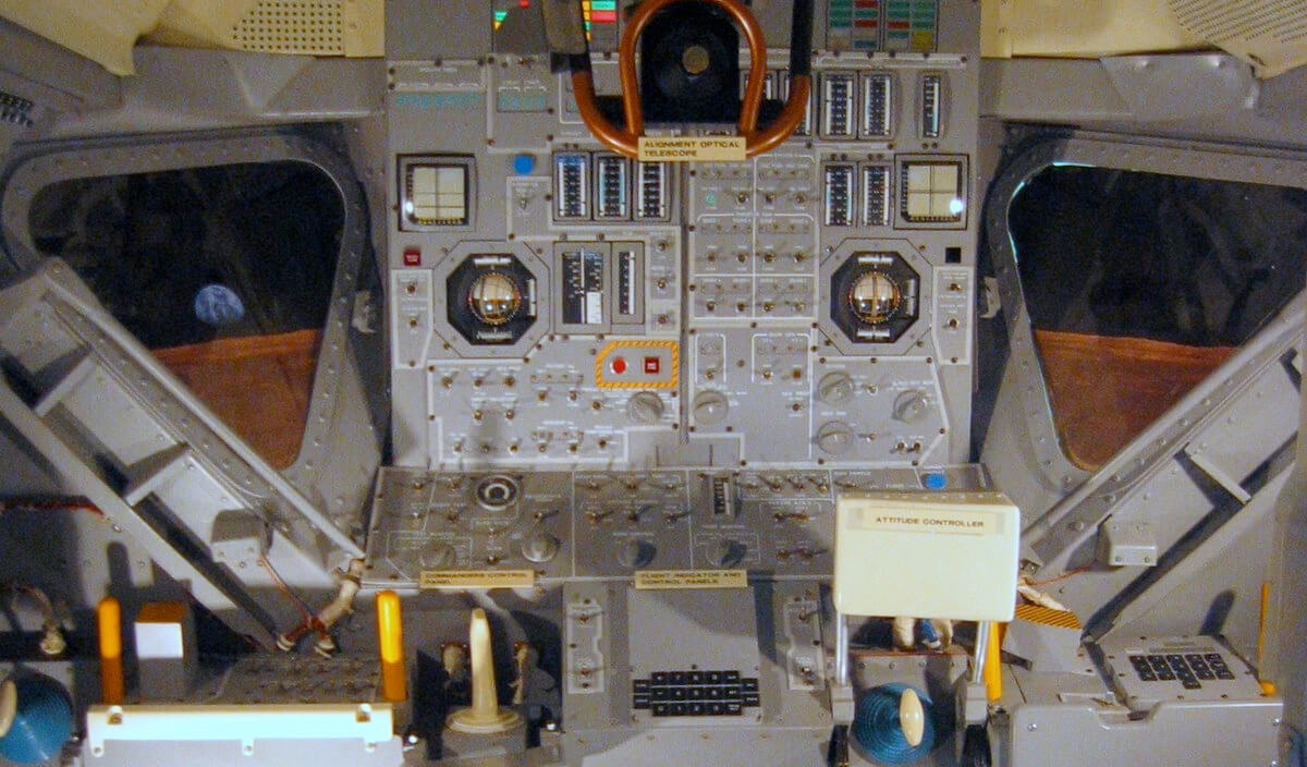 Inside an Apollo lunar module mock-up. The Abort and Abort Stage pushbuttons are outlined in caution tape on the left (CDR) side of the central instrument panel.