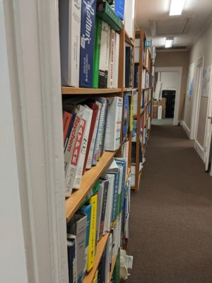 A tightly packed bookshelf is a significant RF obstacle,—worth a couple of walls in its own right—even when traversed perpendicularly. Penetrating its <em>length</em> is an absolute no-go.