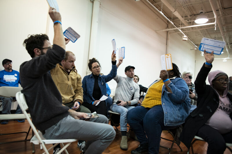 Voters hold up presidential preference cards during the first-in-the-nation Iowa caucus at the Southridge Mall in Des Moines.