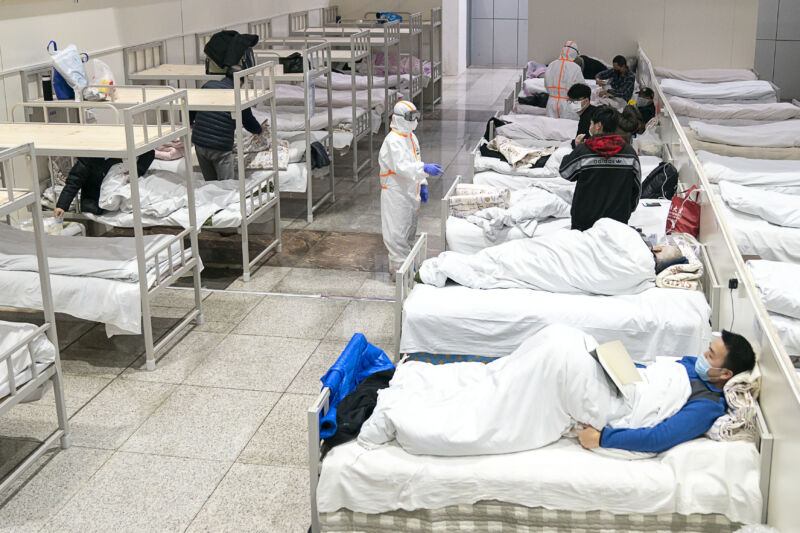 A tech in protective gear inspects patients in a row of beds.