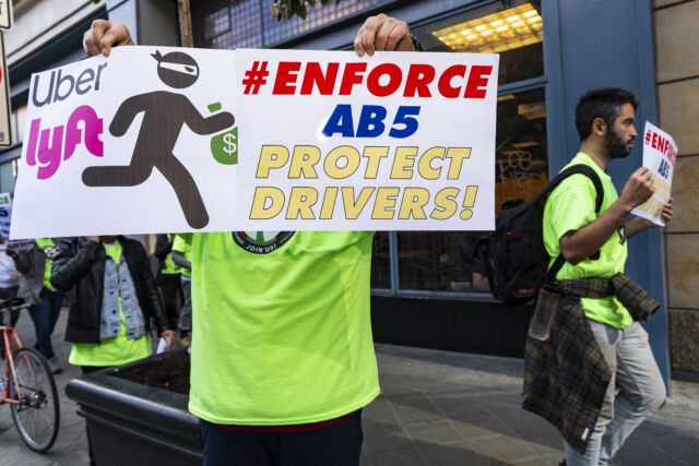 In light of AB 5, Uber and Lyft drivers hold placards during a protest against the ridesharing companies' low wages in Los Angeles, California.