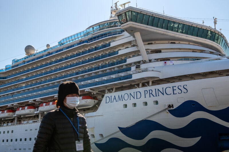 A person wearing a face walks along a harbor on a sunny day with a Princess Diamond cruise ship anchored in the background.