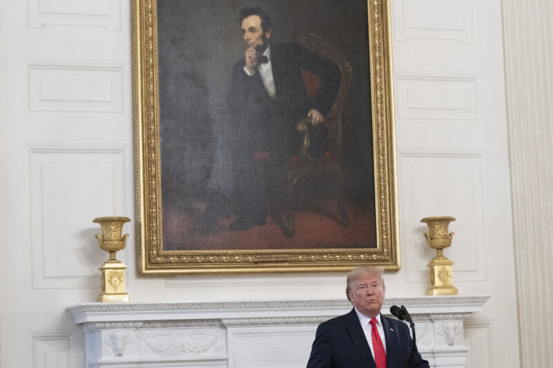 A man speaks from a podium while being dwarfed by a painting of Abraham Lincoln.