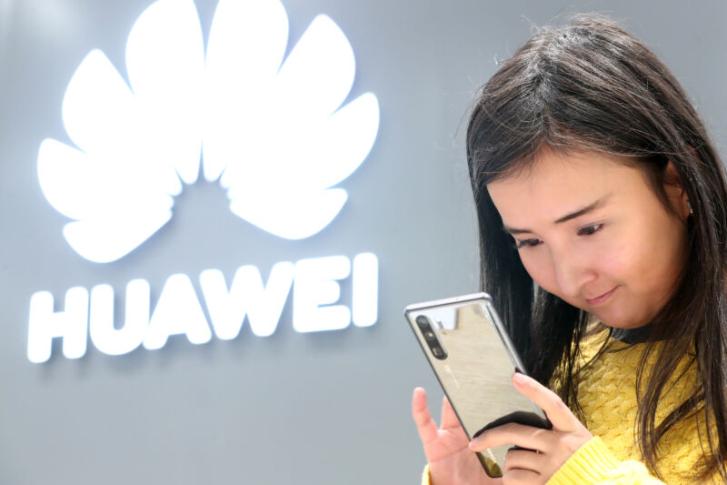 A customer looks at a Huawei smartphone in a Huawei store in Moscow.