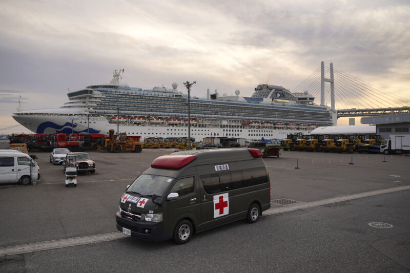 An ambulance sits in a parking lot in front of a docked cruise ship.