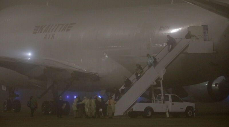 Passengers use mobile stairs to exit and jet plane at night.