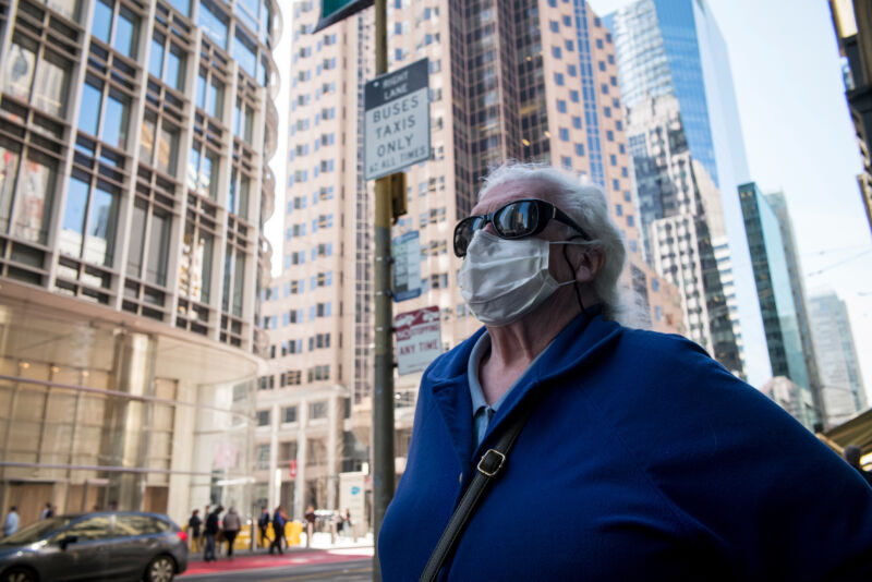 A pedestrian wearing a protective mask stands on Mission Street in San Francisco, California, on Thursday, Feb. 27, 2020. California is monitoring 8,400 people for signs of the virus after they traveled to Asia.