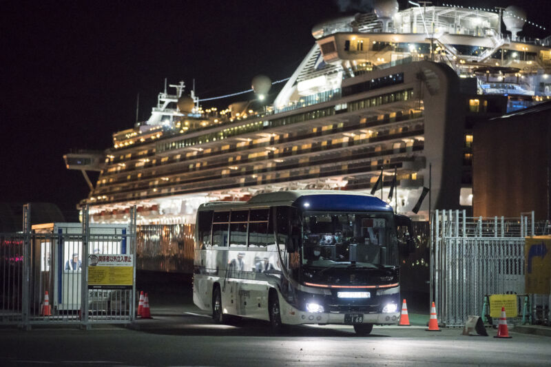 A charter bus drives away from a cruise ship at night lit up like a Christmas Tree.