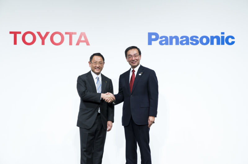 Two Japanese executives shake hands