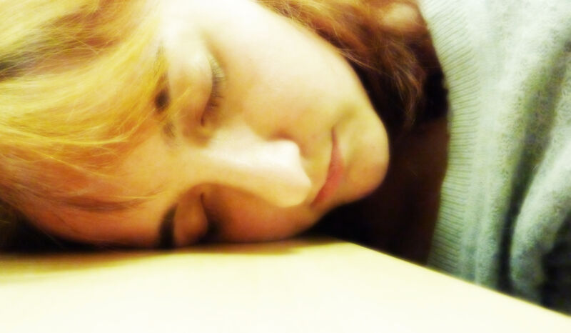 Closeup photo of a woman sleeping with her head on a desk.