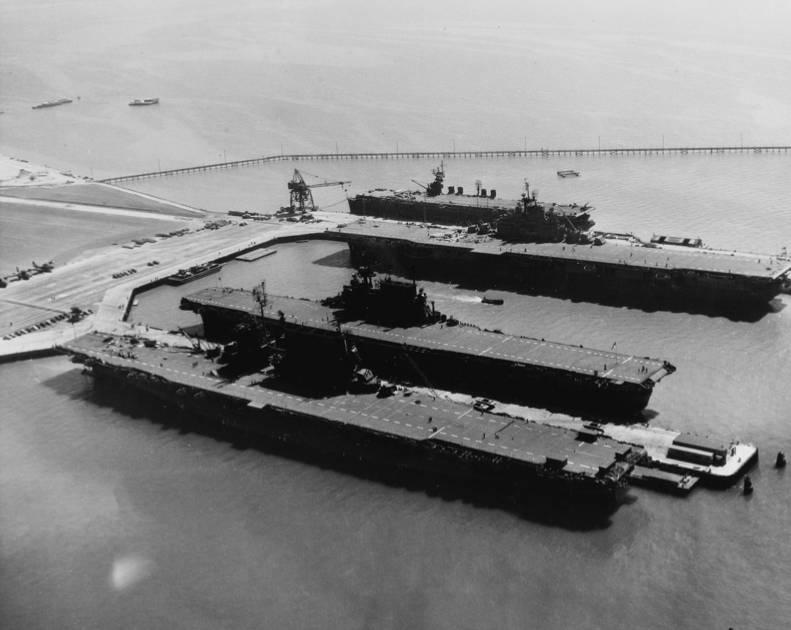"""Three American fleet carriers at NAS Alameda, along with the light carrier USS <em>San Jacinto</em>, farthest from the camera. Escort carriers were even smaller than the <em>San Jacinto</em>, so this gives a sense of the relative size of escort carriers compared to fleet carriers.""""><img alt="""