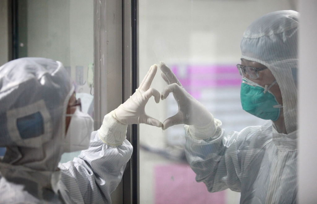 YANGZHOU, CHINA - On Valentine's day, in a isolation ward novel coronavirus pneumonia in Yangzhou Third People's Hospital, a couple of doctors make gesture of love through glass.