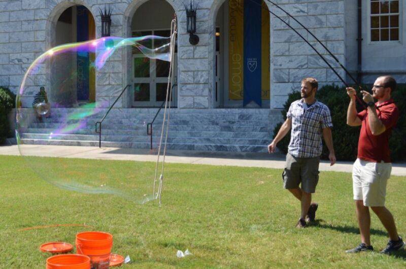 Two grown men blow giant bubbles on a lawn.