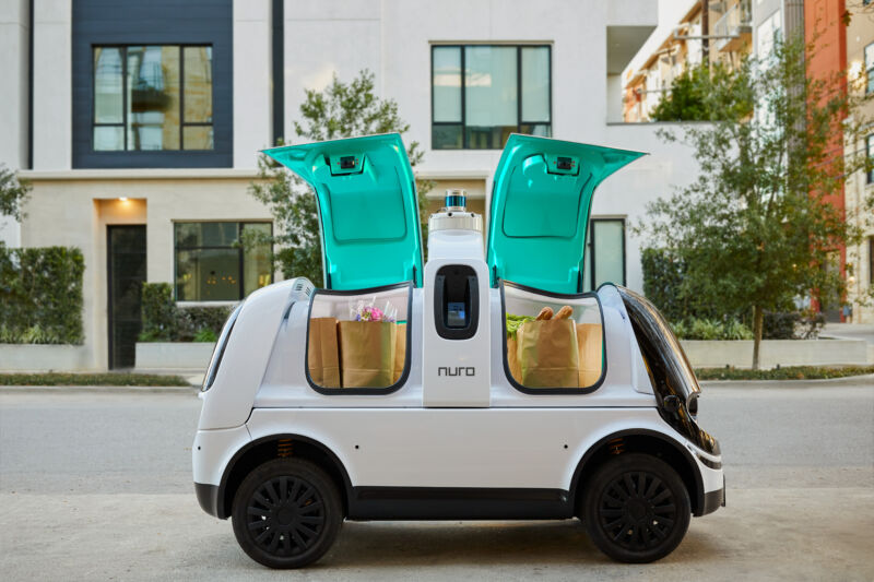 Promotional image of a self-driving, no-passenger vehicle on a sedate urban street.