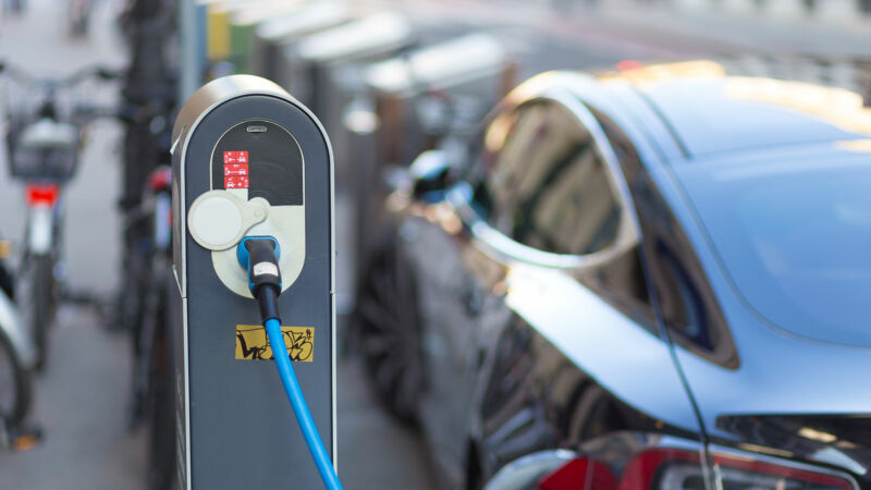 Image of a car plugged into charging hardware.