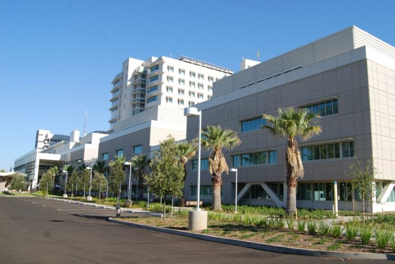 Exterior of teaching hospital with palm trees.