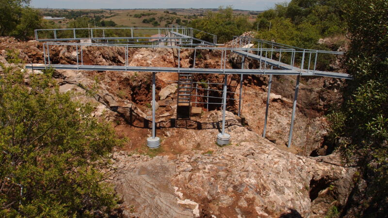 A network of elevated metal walkways rings a rocky pit.