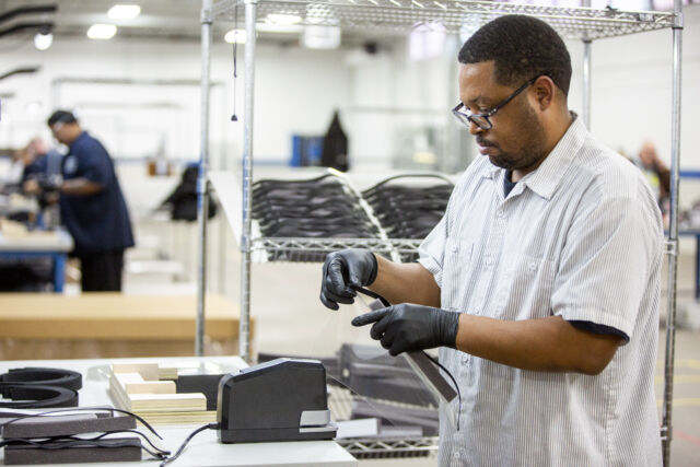 Operators and assemblers assemble medical face shields. Ford is aiming to produce 100,000 plastic face shields per week.