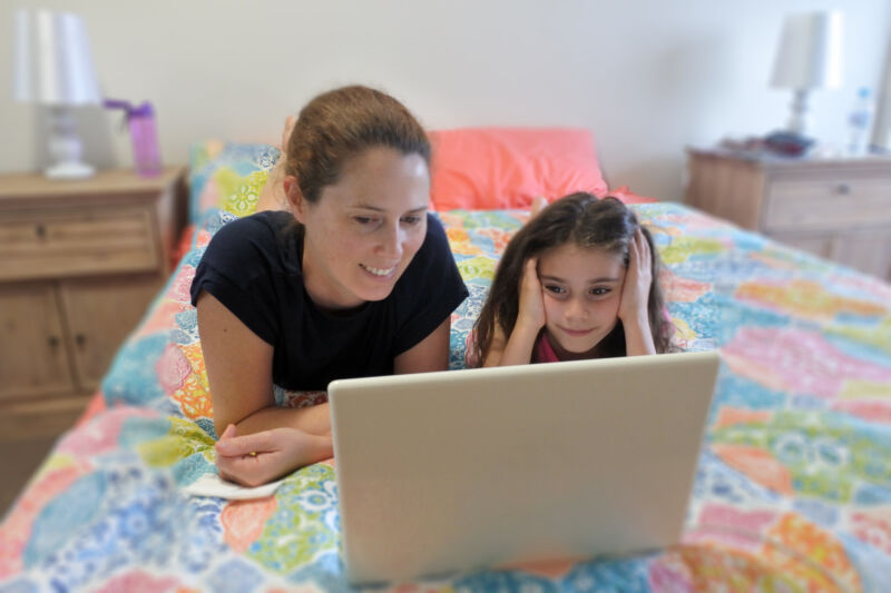 A mother and child daughter look at a laptop together.