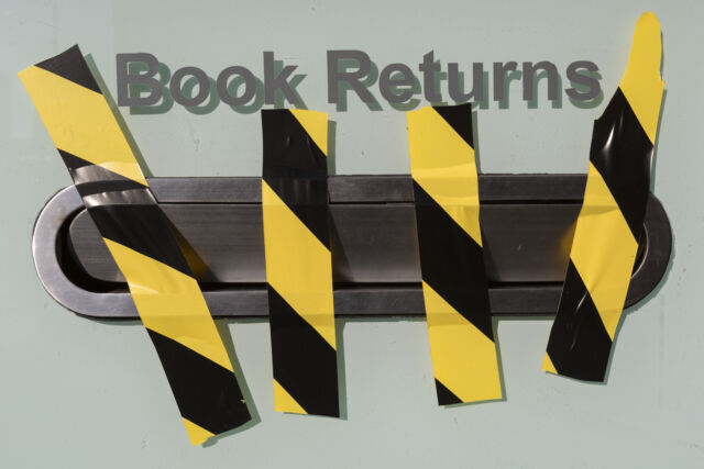 Hazard tape blocks the book returns slot at a London library.