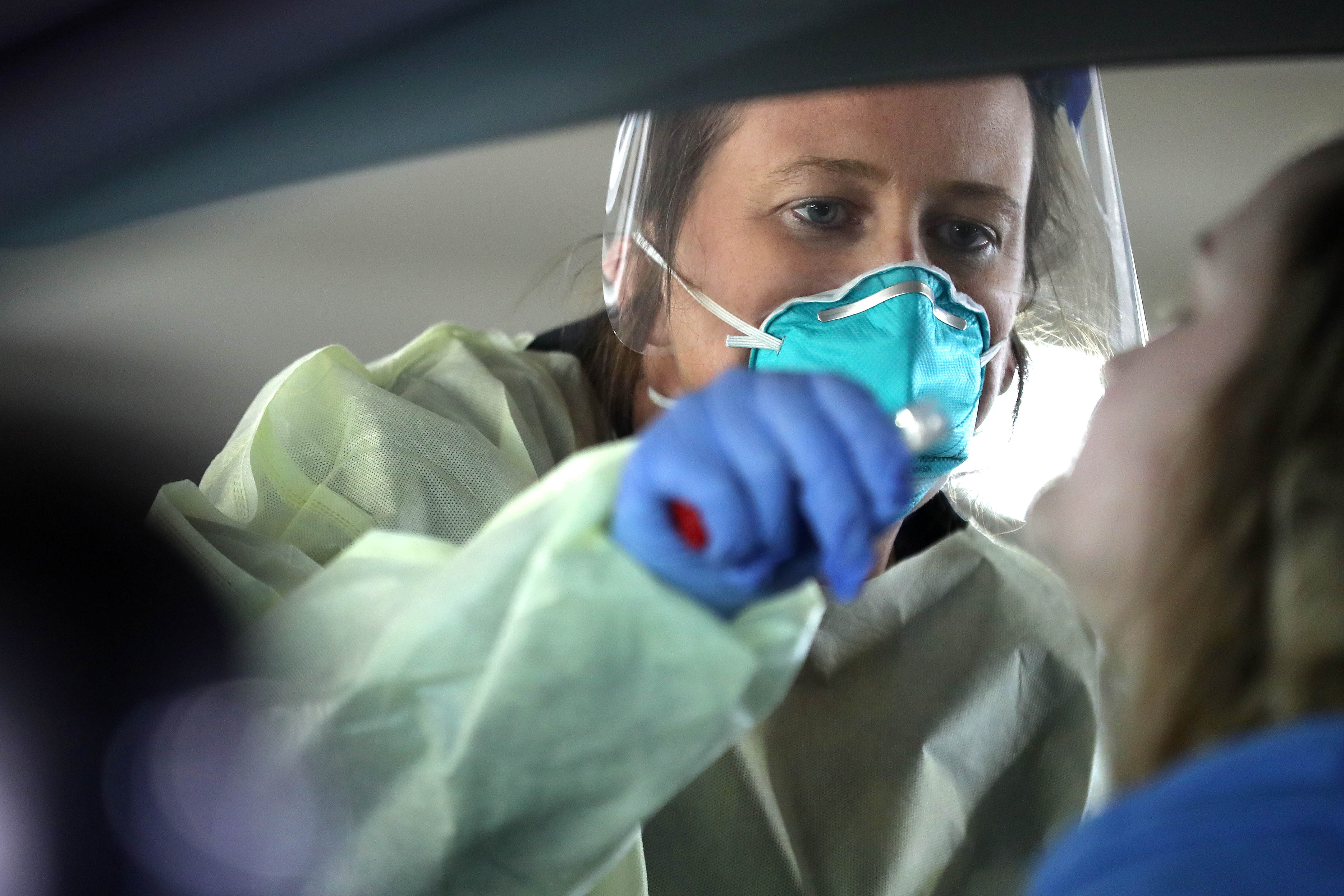 Dawn Canova, clinical manager for outpatient wound care at Carroll Hospital, takes samples from people to test them for the coronavirus at a drive-thru station in the hospital's parking garage while wearing a medical grade mask.