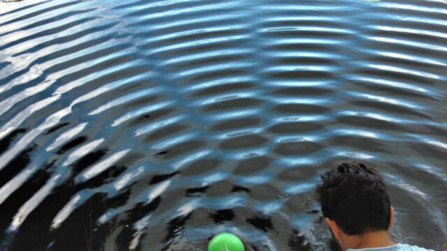 Water waves from two sources (one visible in green, the other hidden behind the moderator). The circular waves overlap into areas of added strength (light stripes) and areas where the waves cancel each other (dark bands). The formation of stripes is a signature of the wave motion.
