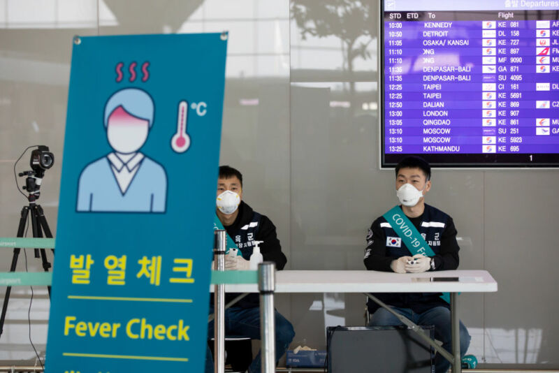 South Korean soldiers wearing protective masks sit at a temperature screening point at Incheon International Airport in Incheon, South Korea, on Monday, March 9, 2020. The coronavirus outbreak in South Korea is showing signs of slowing as the rate of new daily infections falls and health authorities almost finished testing members of a religious sect at the center of the epidemic, the country's health minister said.