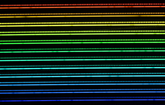 A folded spectrum from the High Accuracy Radial velocity Planet Searcher (HARPS) at the La Silla Observatory in Chile. The bottom line is the spectrum of a star with characteristic absorption lines (dimmer/narrower regions), while the top line is the spectrum of an optical frequency comb from a pulsed laser to provide absolute color reference. The individual beams of the optical comb can be clearly seen and are used to measure tiny doppler shifts in the star's spectrum due to orbiting planets.