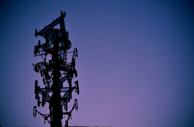 A cell phone tower at dusk.