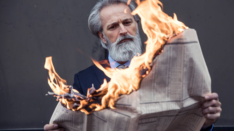 Stock photo of a gloriously bearded man reading a newspaper that's on fire.